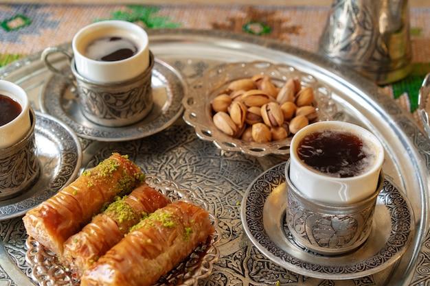 Baklava arabo tradizionale del dessert con una tazza di caffè turco
