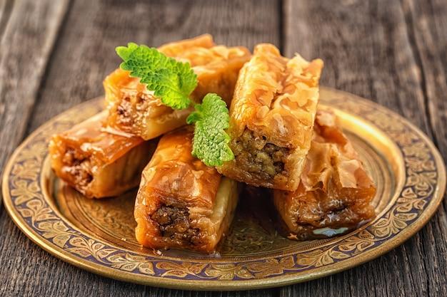 Baklava arabo tradizionale del dessert con miele e noci, fuoco selettivo.