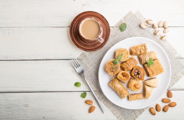 Dolci arabi tradizionali (kunafa, baklava) e una tazza di caffè su un fondo di legno bianco. vista dall'alto, copia spazio.
