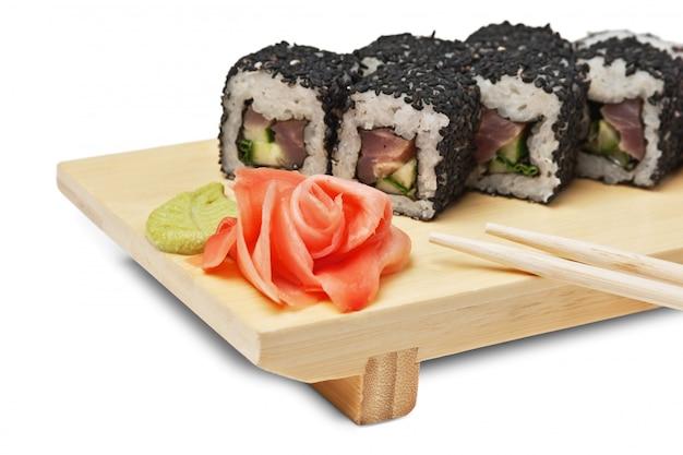 Sushi asiatici tradizionali dell'alimento sul piatto di legno isolato su fondo bianco