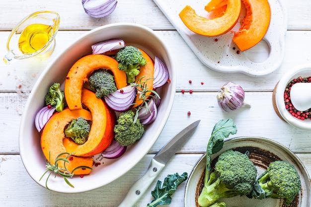 Piatti di zucca autunnali tradizionali. zucca arrostita alla griglia con spezie, olio d'oliva, erbe, broccoli e cipolle. su una teglia da forno, su uno sfondo bianco in legno rustico. vista dall'alto.