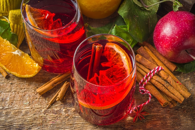 Bevanda alcolica tradizionale autunno inverno. sangria fruttata autunnale calda con agrumi, mele e spezie, fondo rustico in legno Foto Premium