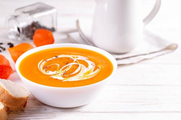 Piatti tradizionali autunnali e invernali, zuppa di zucca calda e piccante, panna e baguette appena sfornate su un tavolo bianco, copia dello spazio