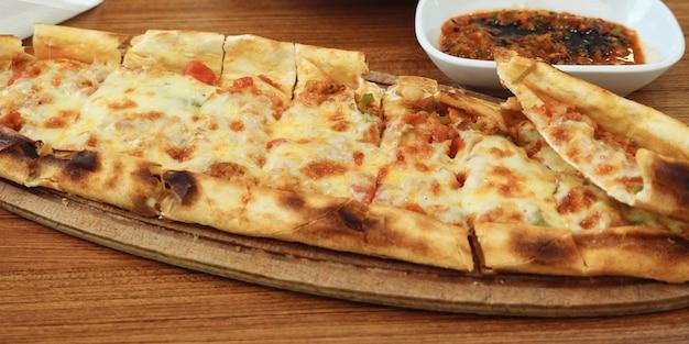 Pranzo tradizionale azero con pane fresco khachapuri ripieno di formaggio suluguni e verdure. khachapuri su tavola di legno, primo piano.