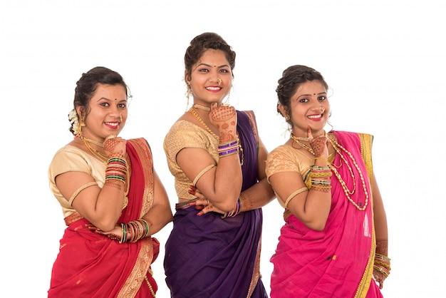 Tradizionali belle ragazze indiane in saree in posa su uno spazio bianco