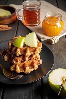 Cialde belghe tradizionali con mela verde a fette, miele e una tazza di tè per colazione. composizione sulla superficie in legno scuro.