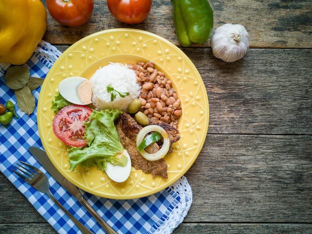 Piatto di cibo brasiliano tradizionale fagioli carne di riso e insalata vista dall'alto.