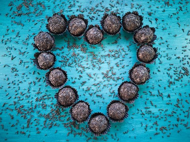 Brigadeiro dolce brasiliano tradizionale che forma il cuore sulla tavola blu.