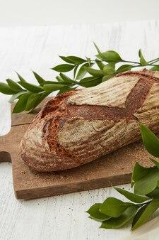 Pane tradizionale su tavola di legno con rami di foglie verdi