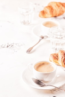 Colazione tradizionale con croissant freschi su sfondo bianco, verticale.