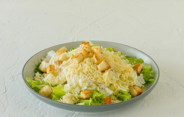 Insalata di cesare tradizionale in un piatto su un tavolo bianco con foglie, salsa, crostini di pane e parmigiano.