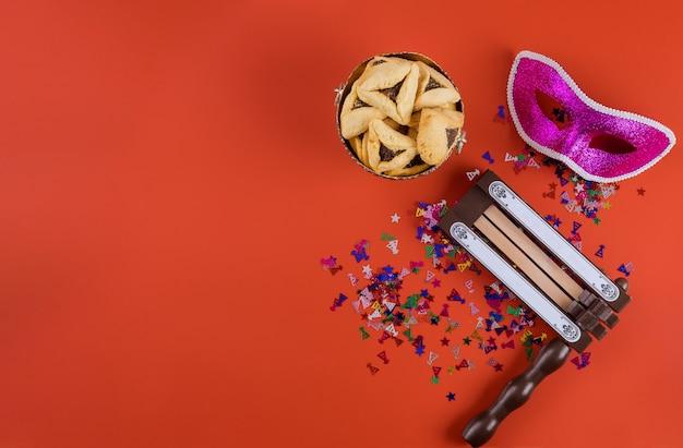 Celebrazione tradizionale durante la festa ebraica purim nei biscotti kosher hamantaschen, rumorista e maschera di carnevale