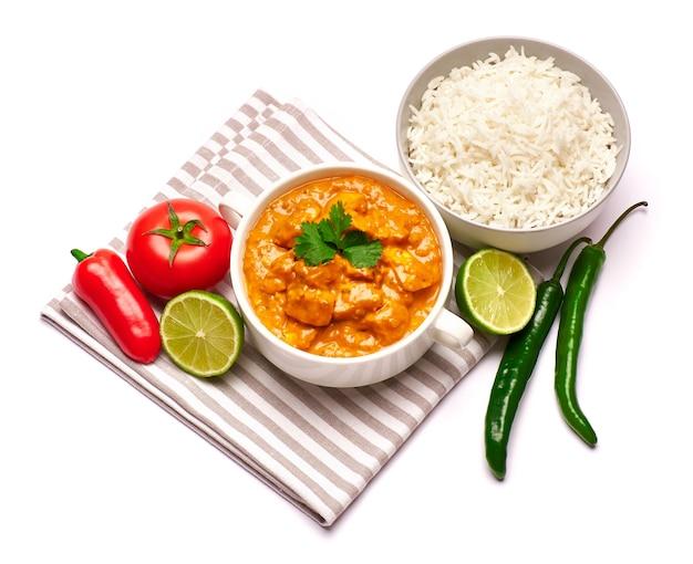 Pollo al curry tradizionale e una ciotola di riso bollito isolato