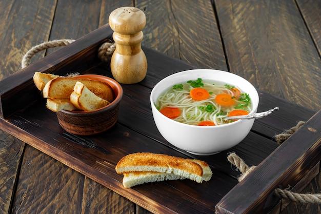 Zuppa di pollo tradizionale con tagliatelle e carote servita in una ciotola su sfondo di legno.