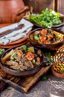 Zuppa tradizionale cilena con carne alla griglia, cipolla e patate servita in piatti di terracotta