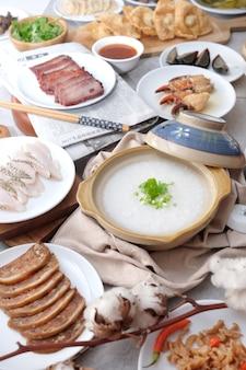 Porridge cinese tradizionale sulla ciotola con la bacchette