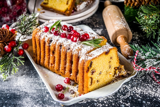 Tradizionale cottura natalizia, torta di frutta natalizia con frutta secca, liquore e decorazioni di mirtilli rossi. torta di frutta fatta in casa su sfondo decorato di natale