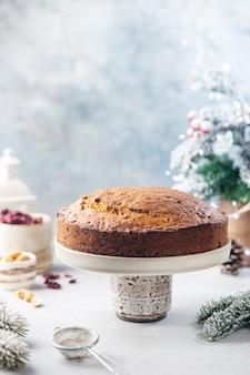 Budino di torta di natale tradizionale con frutta e noci con sfondo chiaro di decorazioni natalizie