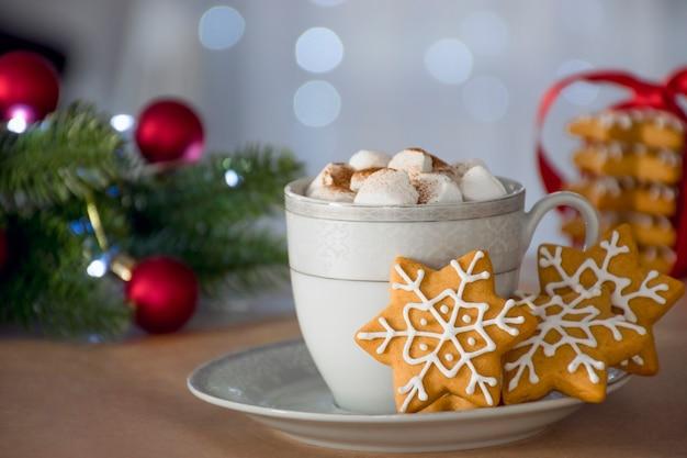 Biscotto di pan di zenzero fatto in casa tradizionale di natale e tazza di bevanda calda invernale con marshmallow, decorazioni festive e bokeh sullo sfondo.