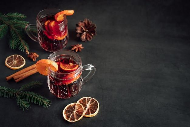 Vin brulè caldo tradizionale di natale. bevanda calda con spezie in tazza di vetro su uno sfondo scuro.
