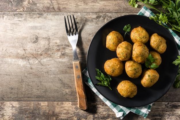 Frittelle di merluzzo tradizionali decorate con aglio e prezzemolo Foto Premium