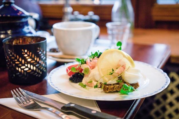 Panini aperti tradizionali danesi smorrebrod con pane di segale gamberi uova sode caviale limone
