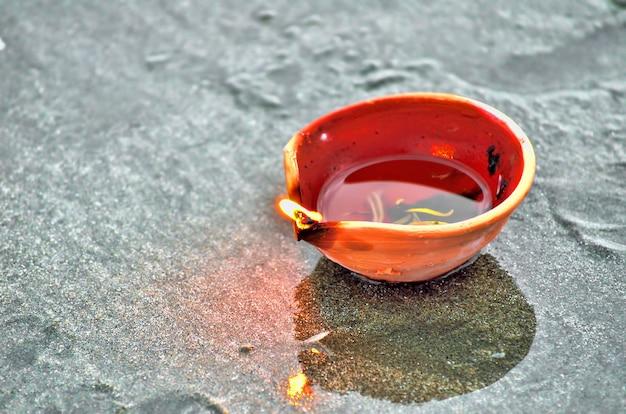 Diwali tradizionali lampade e candele accese sulla spiaggia di sabbia. messa a fuoco selettiva, dof poco profondo e rumore visibile dovuto alla scarsa illuminazione.