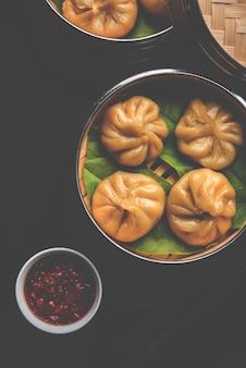 Gnocchi tradizionali momos cibo dal nepal servito con chutney di pomodoro su sfondo lunatico. messa a fuoco selettiva
