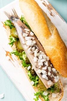 Spuntino olandese tradizionale, panino ai frutti di mare con aringhe, cipolle e cetrioli sottaceto. broodje haring