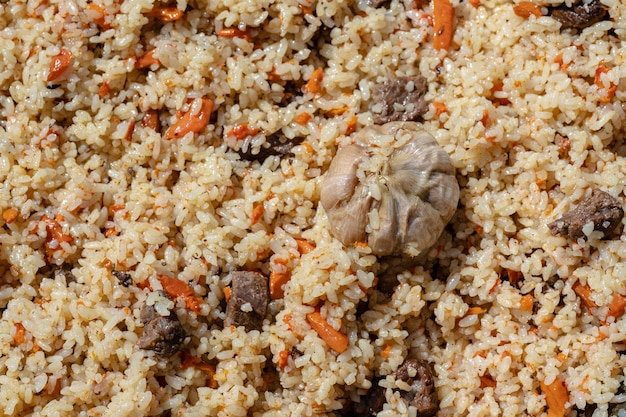 Piatto culinaria tradizionale orientale pilaf ingredienti riso con fettine di grasso di carne e verdure