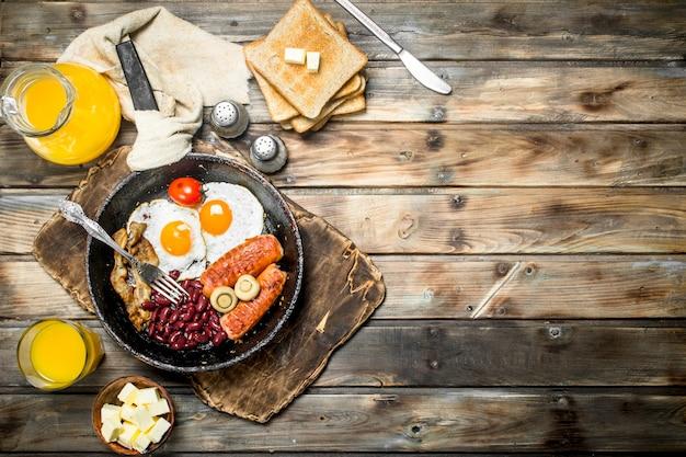 Prima colazione inglese tradizionale. antipasti con pane fritto e succo d'arancia. su una superficie di legno.