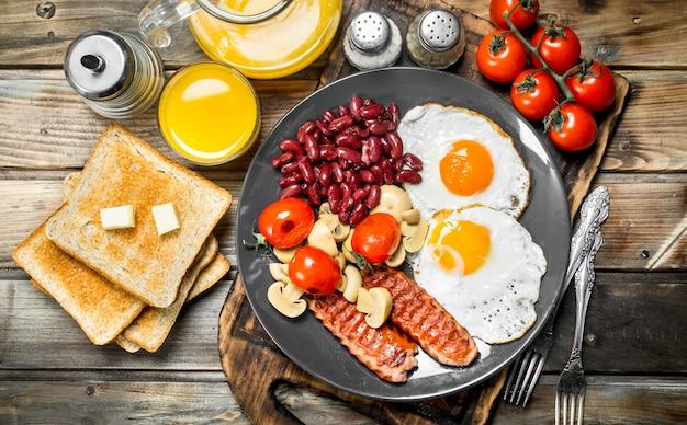 Prima colazione inglese tradizionale. uova fritte con fagioli, salsicce e pane fritto su un tavolo rustico.