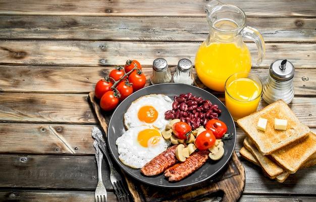 Prima colazione inglese tradizionale. uova fritte con fagioli, salsicce e pane fritto. su uno sfondo di legno.