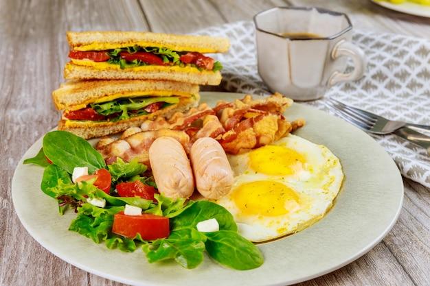 Tradizionale colazione inglese con pancetta, uova, salsicce, insalata e toast di formaggio grigliato.