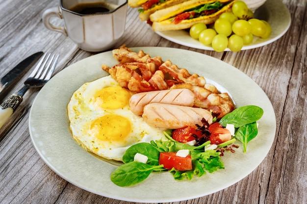 Tradizionale colazione inglese con pancetta, uova, salsicce, insalata e toast di formaggio grigliato