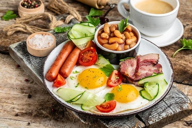 Colazione tradizionale inglese con uova fritte, pancetta, fagioli, caffè e salsiccia, menu del ristorante, dieta, ricetta del libro di cucina.