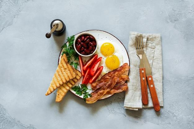 Prima colazione inglese tradizionale con uova fritte, pancetta, fagioli, toast e pomodori su cemento grigio
