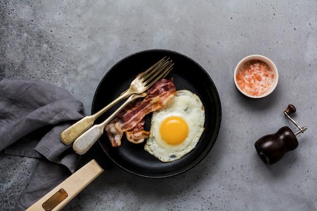 Prima colazione inglese tradizionale con uova fritte e pancetta in padella in ghisa sul vecchio sfondo di cemento grigio. vista dall'alto.