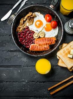 Prima colazione inglese tradizionale con succo d'arancia sulla tavola rustica nera.
