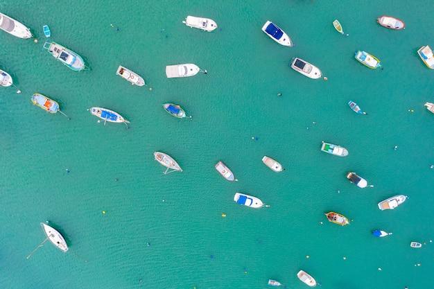 Barche colorate dagli occhi tradizionali nel porto del paesino di pescatori mediterraneo, vista aerea marsaxlokk, malta.