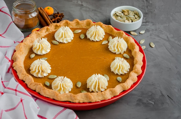 Tradizionale torta di zucca festiva con spezie panna montata e semi dessert per il ringraziamento