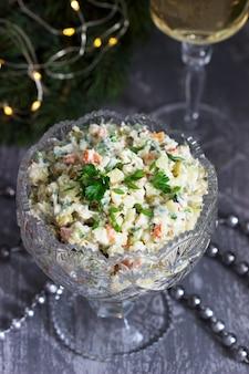 Tradizionale insalata festosa olivier in un vaso di cristallo, servita con vino bianco sullo sfondo delle decorazioni natalizie. messa a fuoco selettiva.