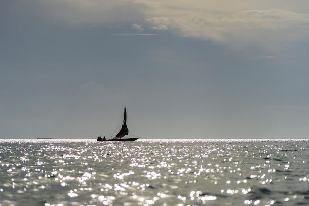 Barca tradizionale di sambuco del pescatore durante il tramonto sull'oceano indiano nell'isola di zanzibar, tanzania, africa orientale