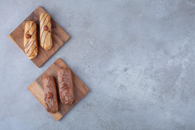 Eclairs francesi tradizionali con cioccolato posto sulla tavola di legno.