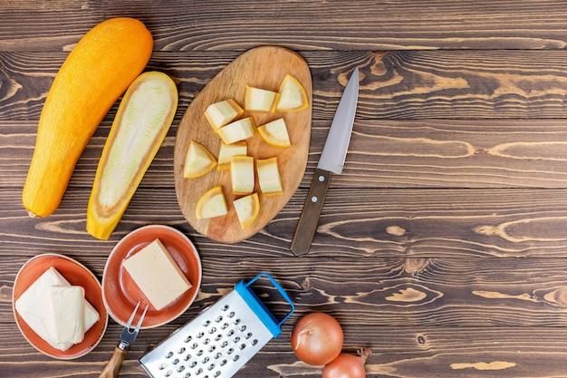 Ricetta francese tradizionale con zucchine, formaggio, cipolla, burro su una superficie di legno con spazio di copia. vista dall'alto.