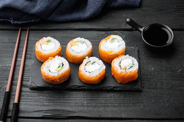 Set di rotoli di sushi giapponesi freschi tradizionali, su tavolo di legno nero