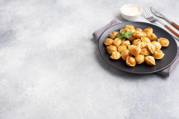 Pelmeni fritti tradizionali, ravioli, gnocchi ripieni di carne su banda nera, cucina russa. sfondo grigio cemento, copia dello spazio.