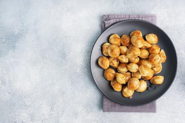 Pelmeni fritti tradizionali, ravioli, gnocchi ripieni di carne su piastra nera, cucina russa. tavolo in cemento grigio, copia dello spazio.
