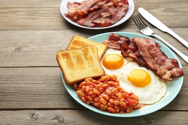 Prima colazione inglese completa tradizionale - uova fritte, fagioli, pancetta e pane tostato sulla tavola di legno grigia
