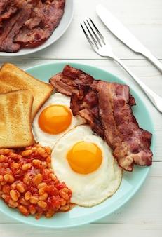 Tradizionale colazione inglese completa uova fritte, fagioli, pancetta e pane tostato sul tavolo bianco